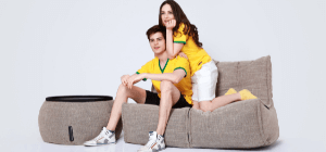 Australian Couple wearing yellow shirts sits on brown bean bag sofa bed with brown ottoman