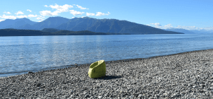 Outdoor green bean bag sofa chair sits on gravel facing the lake under the heat of the sun