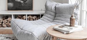 Grey bean bag sofa near fire place beside table