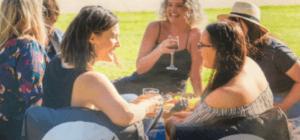 Group of Australian women goes to Moonlight Cinema enjoying their drinks while sitting in a black bean bag sofa chair