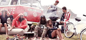 Group of friends having a cookout beside red van while sitting on beige bean bag sofa chairs