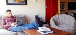 Man in chekered shirt typing on his laptop while sitting on grey bean bag sofa chair