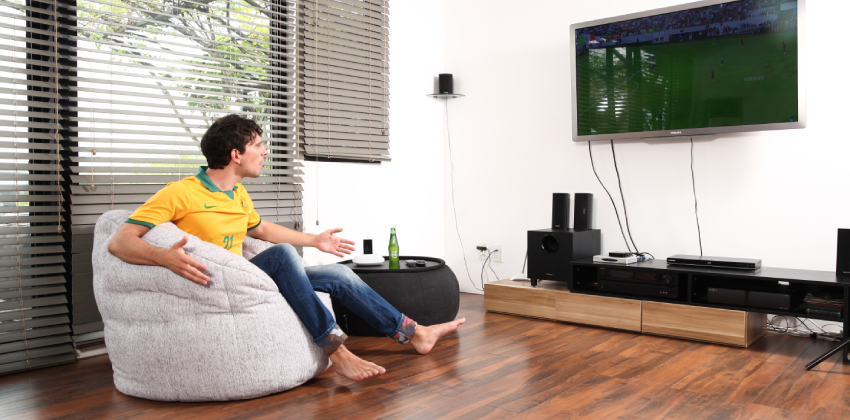 Man watches football match in television in absolute comfort in Butterfly bean bag Sofa