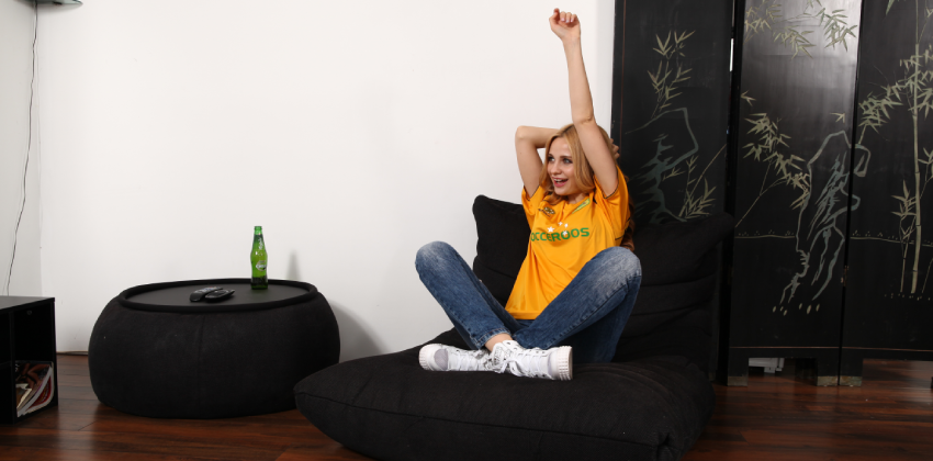 Australian girl cheering ang watching TV during the Olympics 2020 in her black Ambient Lounge bean bag sofa chair