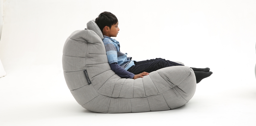 Grey luxury Kids Bean Bag by Ambient Lounge. Young boy in bedroom lounging watching TV