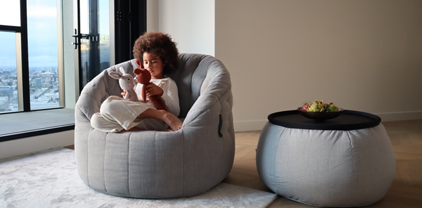 large grey linen luxury kids bean bag by ambient lounge with a girl playing with her stuffed animal toy